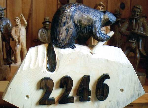 Custom carving  with a beaver over the numbers of a street address